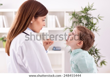 Beautiful doctor examining litle child - stock photo