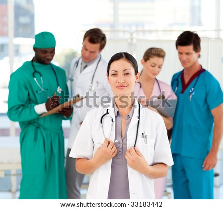 Beautiful doctor with her team in the background in hospital - stock photo