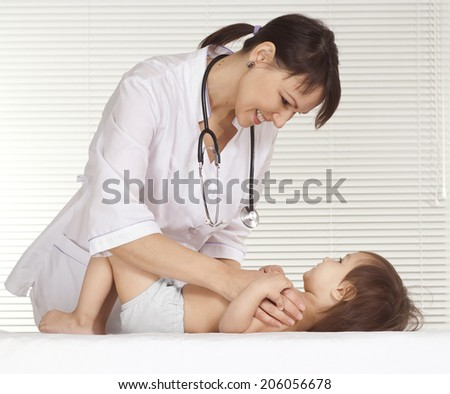 Beautiful doctor with little girl in her office - stock photo
