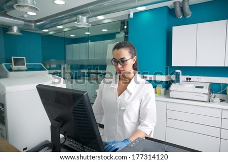 Beautiful Doctor working on the computer in a modern lab  - stock photo