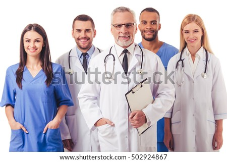 Beautiful doctors in medical coats are looking at camera and smiling, isolated on a white