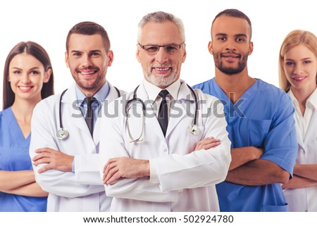 Beautiful doctors in medical coats are looking at camera and smiling while standing with folded arms on a white background