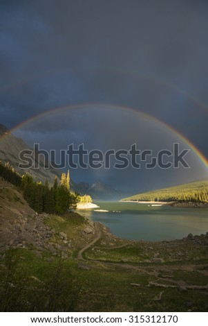 Beautiful double rainbow over scenic Medicine Lake, Jasper National Park in the Canadian Rocky Mountains - stock photo