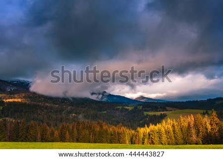 Beautiful dramatic clouds over mountains, covered with spruce forest. Sun spot on the forest glade. Carpathian mountains. Ukraine.