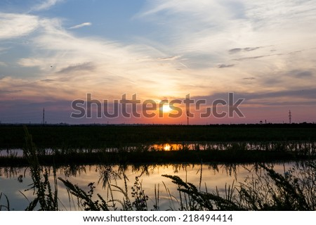 Beautiful, dramatic, colorful clouds and sky at sunset. Electrical wires and stakes and water reflexions. Image has grain texture seen at its maximum size  - stock photo