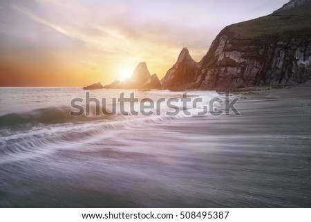Beautiful dramatic sunrise over beach with jagged rocks coastline
