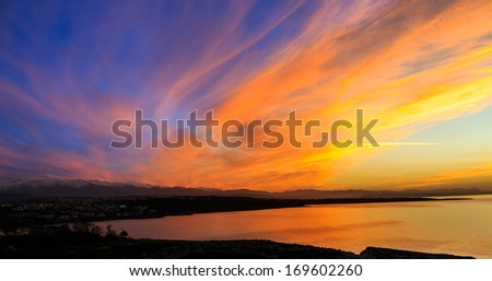 Beautiful dramatic vivid orange sunset over a marine bay turning a swathe of cloud into a fiery band across the twilight sky reflected in the calm tropical ocean below - stock photo