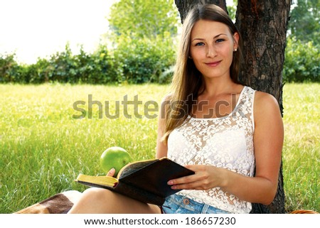 beautiful dreaming girl sitting with a book in the garden in summer - stock photo