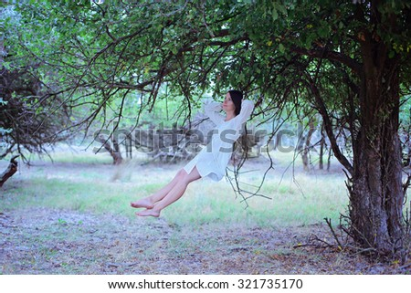 beautiful dreaming relaxing girl levitates between the green trees in the forest - stock photo