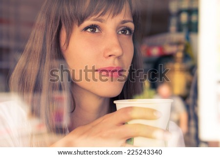 Beautiful dreaming young girl with cup of coffee. Warm color toned image - stock photo