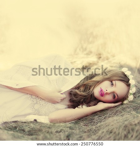 beautiful dreamy blonde girl lying on a meadow in spring - stock photo