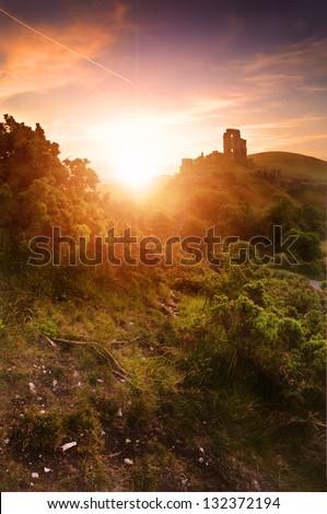 Beautiful dreamy fairytale castle ruins against romantic colorful sunrise - stock photo