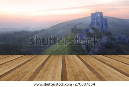 Beautiful dreamy fairytale castle ruins against romantic colorful sunrise with wooden planks floor - stock photo