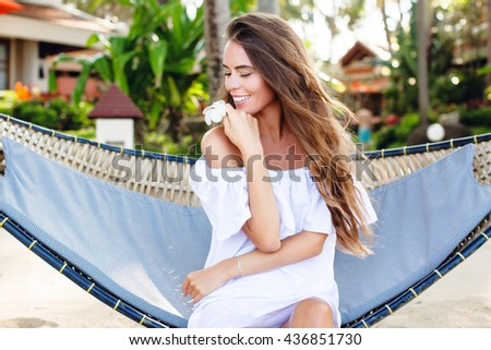 Beautiful dreamy girl sitting in a hammock on a beach with closed eyes smiling widely. She wears white dress with open shoulders and holds a flower in her hand. Girl has long dark hair.  - stock photo