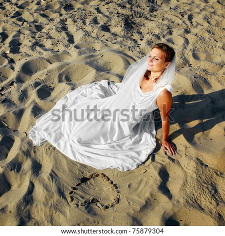 beautiful dreamy slavonic bride laying on sand with heart layed from stones - stock photo