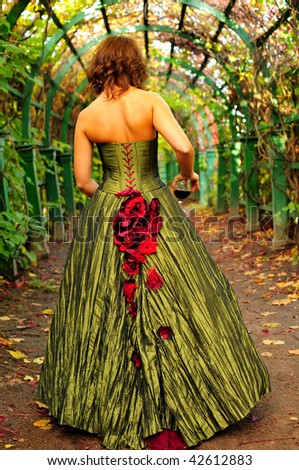 Beautiful dress. Princess with the glass of red wine in the park. View from the back.
