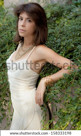 Beautiful Dressed Up Woman Leaning Against Wall With Vines