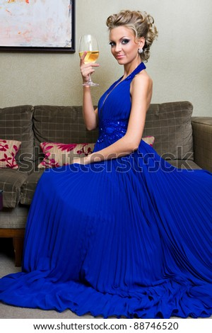 Beautiful dressed woman with a glass of wine in an evening dress - stock photo