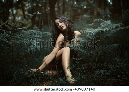 Beautiful dryad finds peace in the woods.  Fantasy and ethereal - stock photo