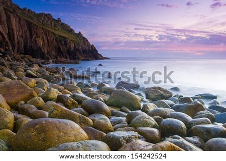 Beautiful dusk at the remote Porth Loe Cove Cornwall England UK - stock photo