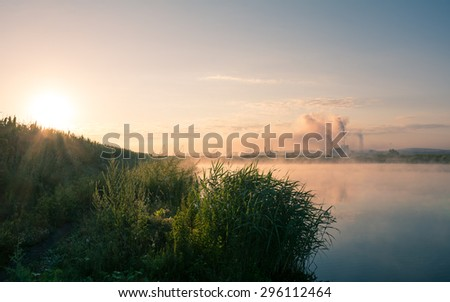 Beautiful early morning mist over a lake and a factory pipe polluting air in the distance. Environmental problems background - stock photo