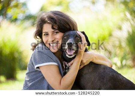 Beautiful early 40s woman hugging her black labrador retriever dog at a park - stock photo