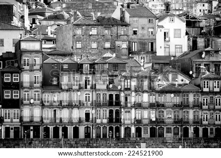 Beautiful early sunlight shedding light on the traditional quaint houses in the old, vintage and touristic ribeira district of Porto, Portugal. in black and white image - stock photo