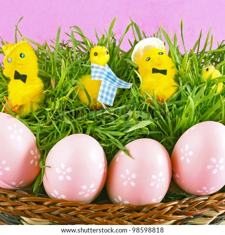 Beautiful easter basket with chicken and decorated eggs in green grass