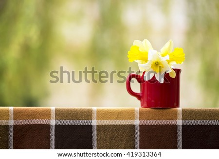 Beautiful Easter daffodil flowers in a red cup - stock photo