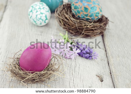 Beautiful Easter egg in a small nest with spring flowers and more eggs in background. Selective focus on egg in foreground. - stock photo