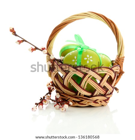 Beautiful easter eggs and apricot blossom in basket, isolated on white