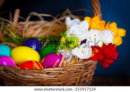 beautiful easter eggs and flowers freesia in wicker basket holiday food background