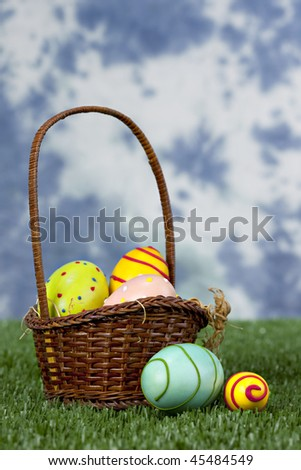Beautiful Easter eggs in brown basket in grass in front of blue and white sky