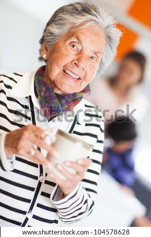 Beautiful elder woman drinking coffee at home - stock photo