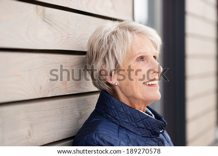 Beautiful elderly lady standing leaning against a wooden building reminiscing with a nostalgic expression on her face - stock photo