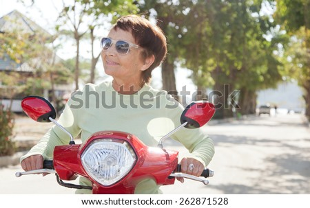 beautiful elderly woman on motorbike - stock photo