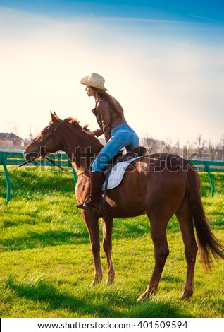Beautiful elegance back woman cowgirl, riding a horse. Clothed blue jeans, brown leather jacket and hat. Has slim sport body. Portrait nature. People and animals. Equestrian.  - stock photo