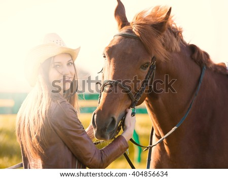 Beautiful elegance woman cowgirl nearby muzzle horse. Has smiling face, brown leather jacket and hat. Has slim body. Portrait nature. People and animals. Equestrian. Close up riding