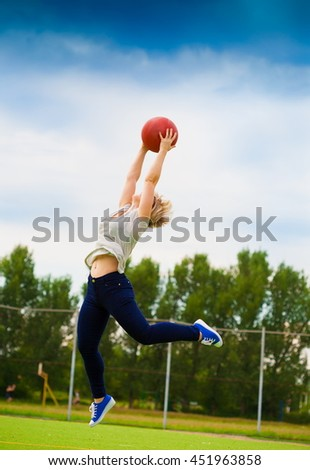 Beautiful elegance woman, has sport athletic sexy slim body, blonde hair, clothed in gray t-shirt and blue jeans, sunglasses, jumping with basketball. Urban city stadium