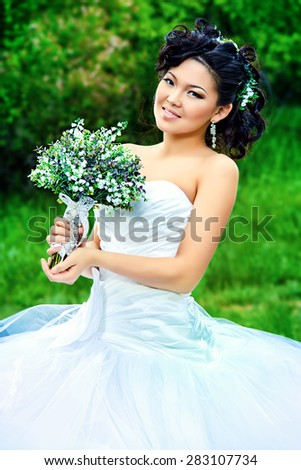 Beautiful elegant asian bride in a summer park. Wedding dress and accessories.  - stock photo