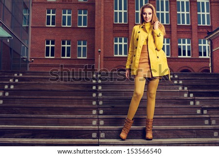 Beautiful elegant blonde woman in autumn clothes standing on the stairs - stock photo