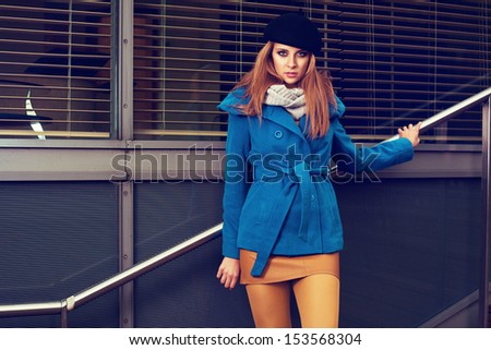 Beautiful elegant blonde woman in autumn clothes standing on the stairs