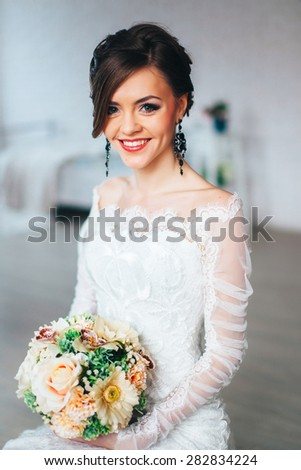 beautiful elegant girl  bride siting on a chair. Portrait of a girl with beautiful makeup and hairdo.