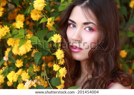 beautiful elegant girl in a pink near shrub with yellow flowers