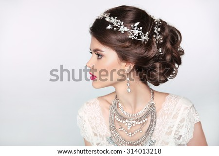 Beautiful elegant girl model with jewelry, makeup and retro hair styling. Isolated on studio background. - stock photo