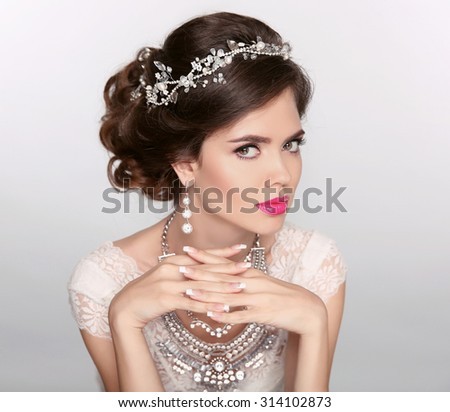 Beautiful elegant girl model with jewelry, makeup and retro hair styling. Manicured nails. Isolated on studio background.