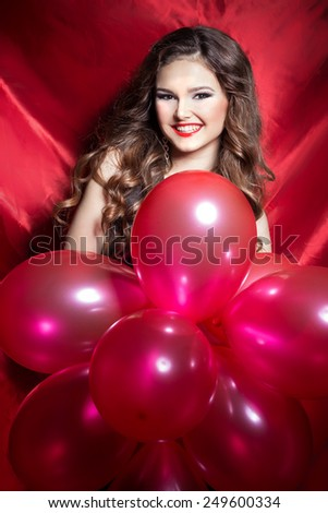 beautiful elegant happy young woman with red balls in hands with red lipstick - stock photo