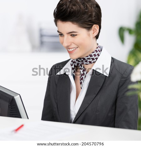 Beautiful elegant hotel receptionist secretary wearing stock photo beautiful elegant hotel receptionist or secretary wearing a stylish neck scarf sitting working at her computer sciox Images