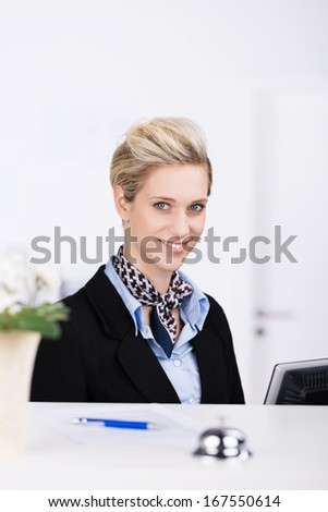 Beautiful elegant hotel young blond receptionist working at her computer at the counter looking up with a warm welcoming smile - stock photo