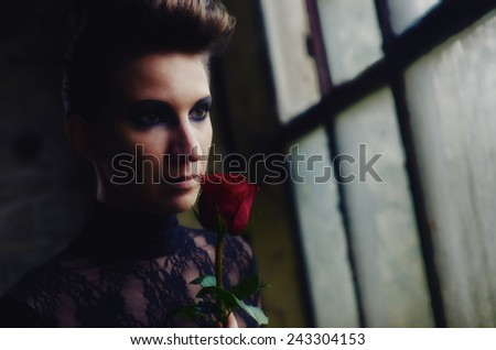 Beautiful elegant lady holding red rose.